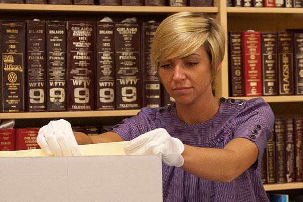 Young lady with short hair wearing gloves looks through box in our 5th floor archives.