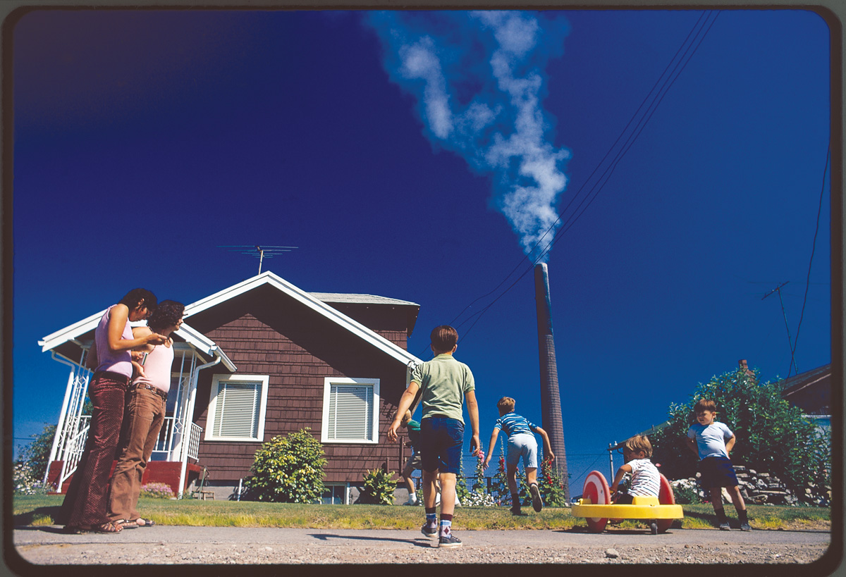 """Children play in yard of Ruston home, while Tacoma smelter stack showers area with arsenic and lead residue."" Gene Daniels, Ruston, Wash., August 1972 National Archives, Records of the Environmental Protection Agency."