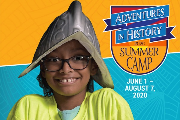 A young girl wears a conquistador helmet