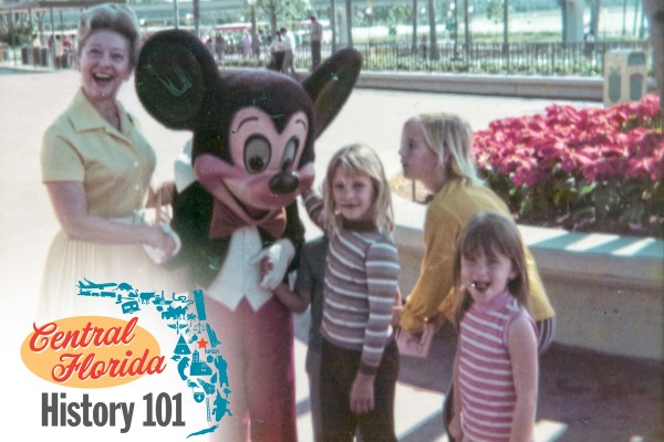 An adult female and four children greet Mickey Mouse in the early days of Walt Disney World