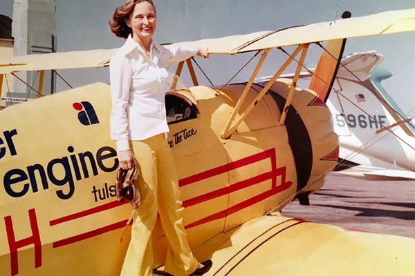 Woman stands on wing of biplane.