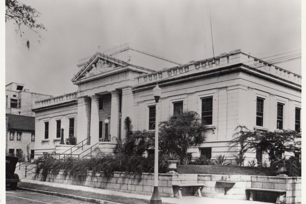 Historic sepia-tone image of the Albertson Public LIbrary, a classic style building with a palm tree in front