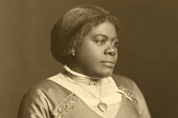 Sepia-toned portrait of Mary McLeod Bethune wearing a high collared dress with a heart necklace