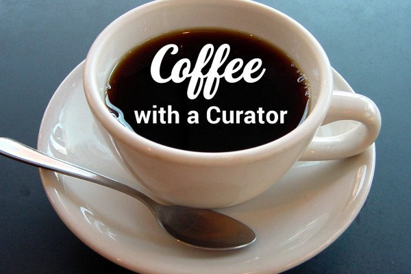 Coffee cup on saucer with spoon with Coffee with a curator text in coffee