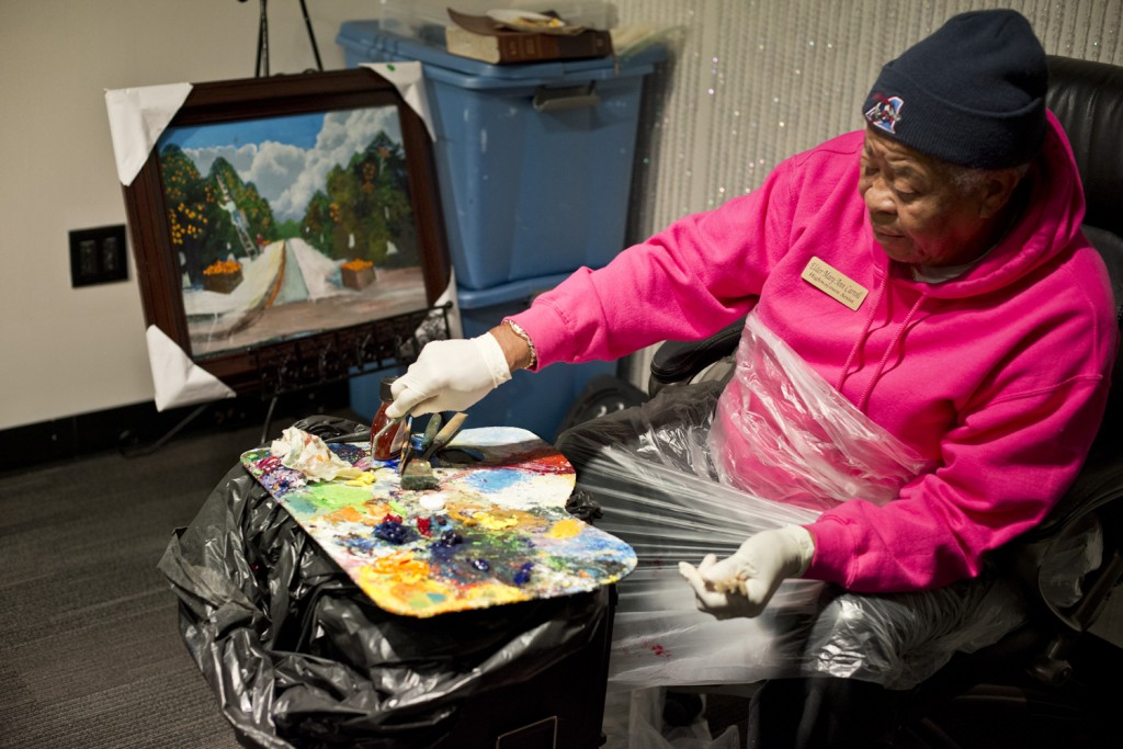 Mary Ann Carroll unpick sweatshirt with palette on her lap and painting on easel.