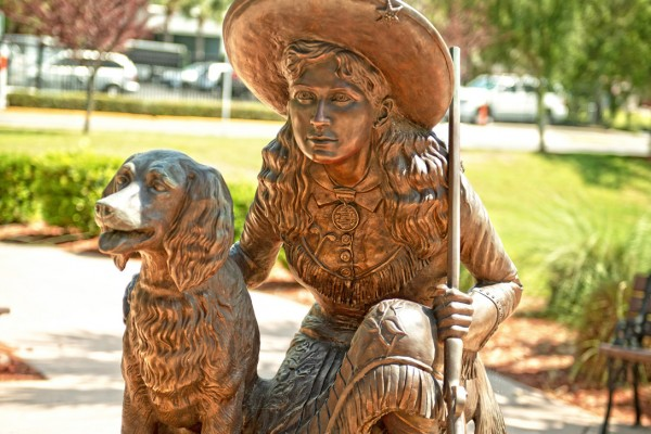 A sculpture of Annie Oakley and Dave the Wonder Dog. Oakley kneels down holding a rifle, Dave is on the opposite side, sitting.