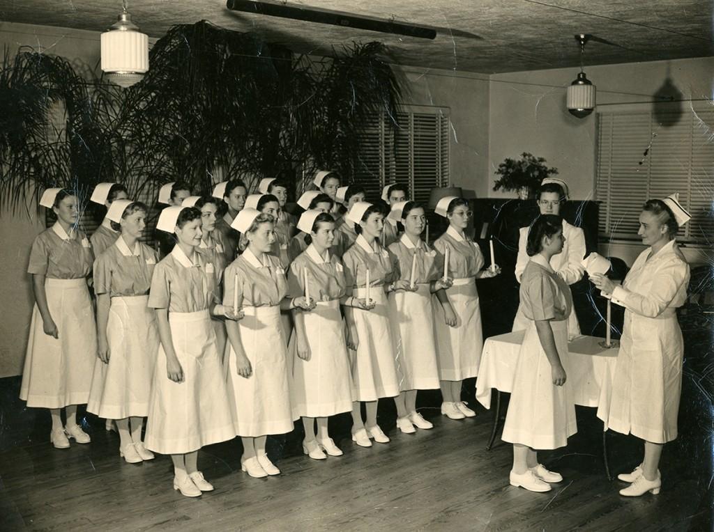 Nurses receive their caps during a graduation ceremony.