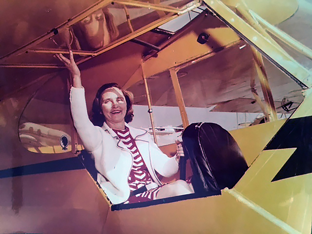 Grace the Ace seated in a yellow biplane