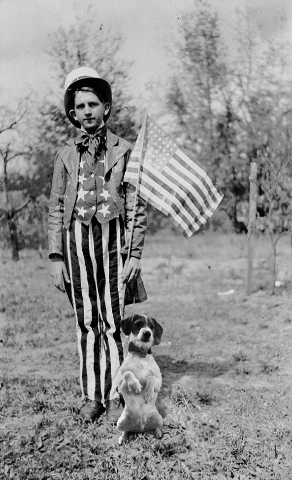 Black and white photo of young man in Uncle San outfit holding an American flag. At his feet is photoshopped dog.