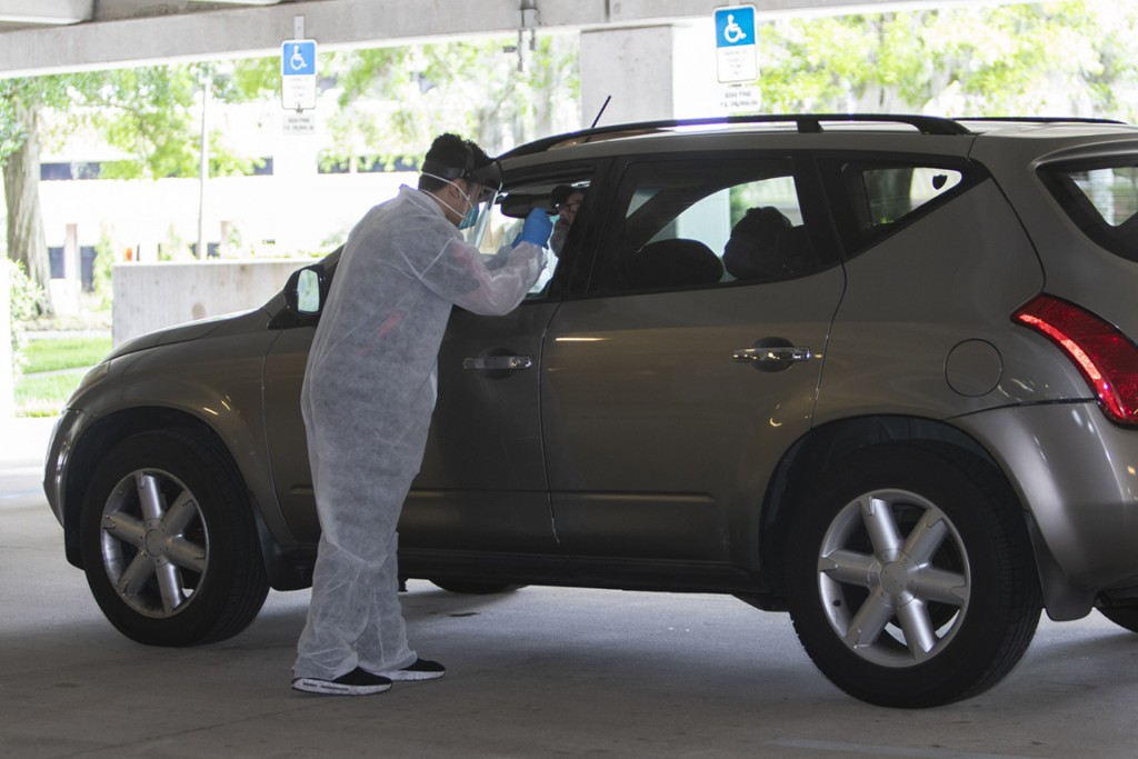 A man in a white jumpsuit and glove administers testing to a man in a car at the University of Central Florida parking garage.